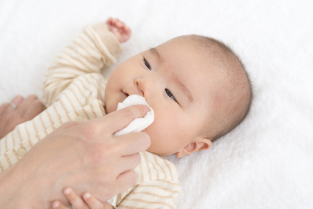 Wipe baby's face on a gauze Standard-Bild