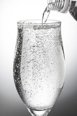 Giet koolzuurhoudend water in een glas