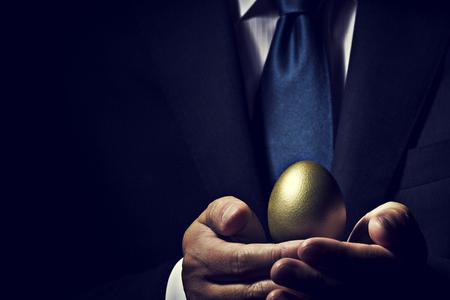 Uomo d'affari che tiene uovo d'oro.