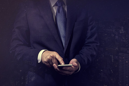 Businessman operating a smartphone.
