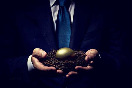 Businessman holding golden egg.