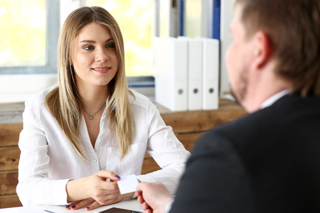 Smiling beautiful woman give blank calling card to male visitor. White collar partners company name exchange, executive or ceo introducing at conference, product consultant, sale clerk concept