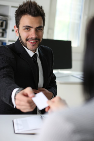 Smiling handsome man in suit give blank calling card to female visitor. White collar partners company name exchange, executive or ceo introducing at conference, product consultant, sale clerk concept