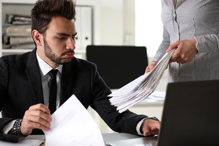 Female employee show pack of documents to busy male manager or boss give extra work to executor. White collar portrait, contract approval, headache and depression, irs, lot of new problems concept