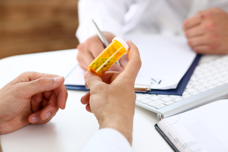 Male medicine doctor write prescription at worktable while patient hand hold jar of pills. Panacea and life save, prescribing treatment, legal drug store concept. Empty form ready to be used Standard-Bild