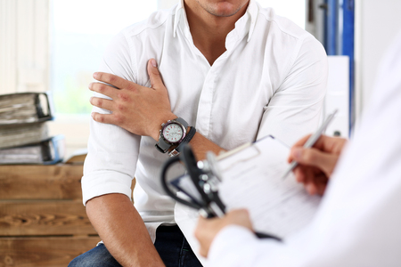 Male doctor hold silver pen filling patient history list at clipboard pad. Physical, exam, er, trauma pain, disease prevention, ward round, 911, prescribe remedy, healthy lifestyle concept Stock Photo