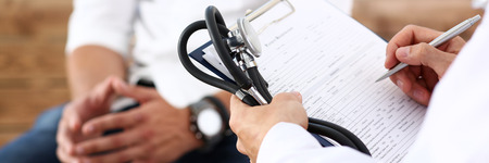 Mannelijke dok van de de greep zilveren pen van de artsenhand vullende geduldige geschiedenislijst bij klembordstootkussen. Lichamelijk, examen, eh, ziektepreventie, wijkronde, bezoekcontrole, 911, remedie voorschrijven, gezond leefstijlconcept