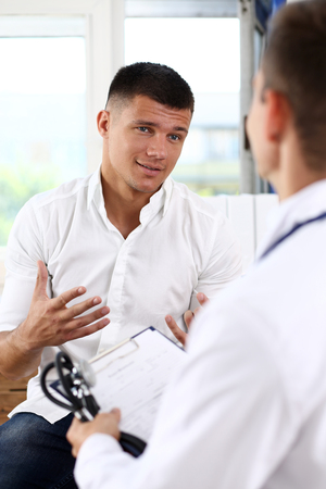 Male patient portrait with doctor filling patient history list at clipboard pad. Physical, exam, er, trauma pain, disease prevention, ward round, 911, prescribe remedy, healthy lifestyle concept