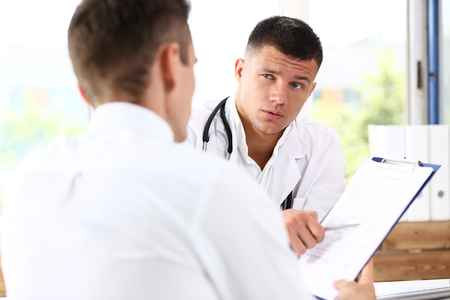 Concerned handsome doctor communicate with patient holding silver pen and showing pad. Physical agreement signature, disease prevention, consent sign, 911, prescribe remedy, healthy lifestyle concept Stock Photo