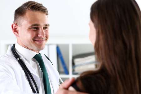 Handsome friendly male doctor talk with thankful female patient at office and greet her with hand on shoulder gesture. Welcoming friend, trust, physical, healthy lifestyle, exam interview concept Foto de archivo