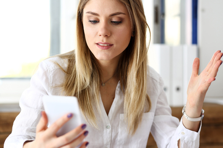 hear business call: Beautiful blonde thoughtful businesswoman look at cellphone in hand portrait. White collar busy life style, electronic device store, online shop, read text, surprised amazed grimace concept Stock Photo