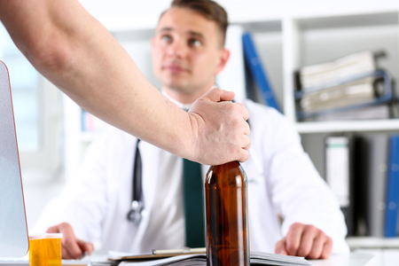 Alcoholic hold in hand empty bottle at doctor reception office closeup. Grief and despair, intoxicated, change life, drunkenness lifestyle, sobriety and temperance, bad habit dependence concept Stock Photo