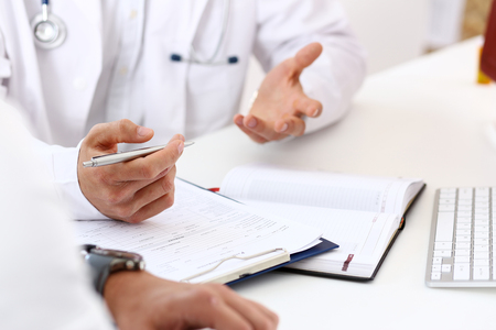 De handen van de betrokken arts bespreken probleem met mannelijke geduldige zilveren de close-up van de holdingspen. Lichamelijk examen, slecht nieuws, ziektepreventie, 911, remedie voorschrijven, gezonde levensstijl, onderwijsconcept