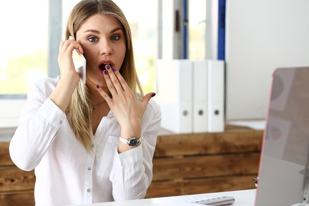 Beautiful blonde thoughtful businesswoman look at cellphone in hand portrait. White collar busy life style, electronic device store, online shop, intrigue, surprised amazed grimace concept Stock Photo