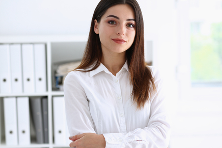 proudly: Beautiful businesswoman brunette portrait in an office in a white shirt stands with crossed hands proudly and independently sympathetic expresses prosperity and success concentrates on your thoughts