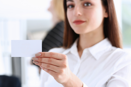 Smiling Business woman in suit hold in hand blank calling card closeup. White collar partners company name exchange, executive or ceo introducing at conference, product consultant, sales clerk concept