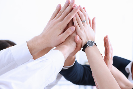 Group of people in suits crossed hands in pile for win closeup. White collar leadership, high five, cooperation initiative achievement, corporate life style, friendship deal, heap, stack concept Stock Photo