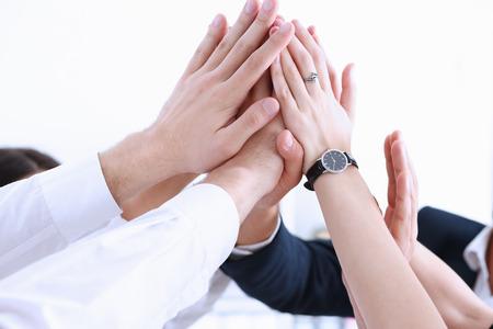Grupo de personas en trajes cruzó las manos en la pila para el primer triunfo. Liderazgo de cuello blanco, cinco altos, logro de iniciativa de cooperación, estilo de vida corporativa, acuerdo de amistad, montón, concepto de pila Foto de archivo - 80899858