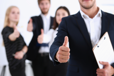 Handsome smiling man showing OK or approval sign with thumb up in creative people office portrait. High level and quality service, job offer, excellent education, advisor, serious business concept Foto de archivo