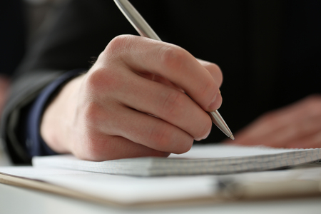Male hand holding silver pen ready to make note in opened notebook sheet. Businessman in suit at workspace make thoughts records at personal organizer, white collar conference, signature concept
