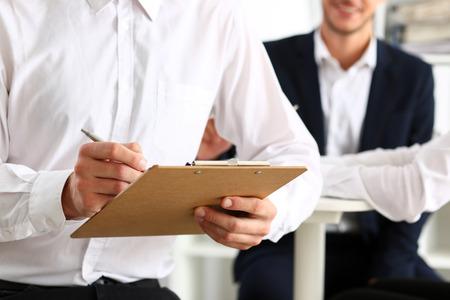 Männlicher Arm im Klagengriff-Silberstift und -auflage, die Anmerkung in der Büronahaufnahme macht. Deal beraten, Lieferunterschrift, Finanzinspektor Job, füllen Umfrageformular, diskutieren Strategie, Projekt Verhandlungskonzept Standard-Bild - 82274754