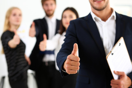 Group of people show OK or confirm with thumb up during conference closeup. High level quality product, serious offer, excellent education, mediation solution, creative advisor participation concept Stock Photo