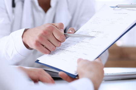 Male doctor hand hold silver pen and showing pad. Physical agreement form signature, disease prevention, ward round reception, consent contract sign, prescribe remedy, healthy lifestyle concept Archivio Fotografico