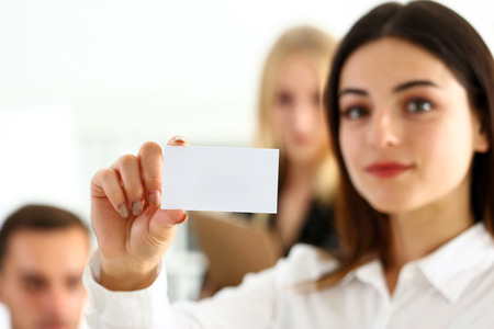 Female hand in suit give blank calling card to visitor closeup. White collar partners company name exchange, executive or ceo introducing at conference, product consultant, sale clerk concept