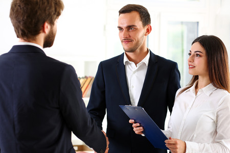 Smiling man in suit shake hands as hello in office portrait. Friend welcome, mediation offer, positive introduction, greet or thanks gesture, summit participate approval, strike arm bargain concept