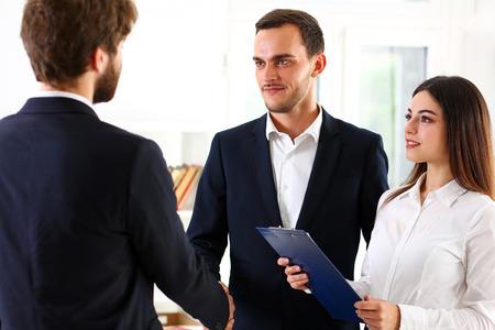 Glimlachende man in pak schudden handen als hallo in kantoorportret. Vriendelijk welkom, bemiddelingsaanbod, positieve introductie, begroeting of dank gebaar, top deelnemen goedkeuring, strike arm koopje concept Stockfoto