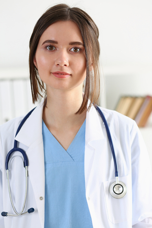 Beautiful smiling female doctor stand in office portrait. Physical and patient disease prevention, exam, er, ward round, 911, prescribe remedy, healthy lifestyle, consultant, nurse profession concept