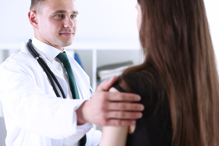Handsome friendly male doctor talk with thankful female patient at office and greet her with hand on shoulder gesture. Welcoming friend, trust, physical, healthy lifestyle, exam interview concept Stock Photo