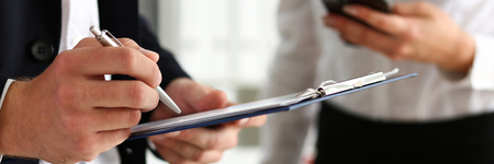 Male arm in suit hold silver pen and pad making note in office closeup. Deal consult, delivery signature, financial inspector job, fill survey form, discuss strategy, project negotiation concept
