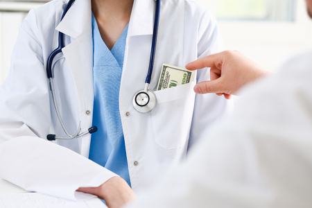 Female medicine doctor chest with bunch of hundred dollars banknotes in pocket. Prestige and high paid job, encash treatment, illegal drug fraud, anonymous visitor, private visit, reform concept Stock Photo