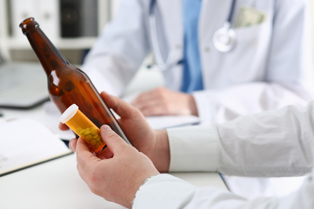 Alcoholic hold in hand empty bottle at doctor reception office closeup. Grief and despair, intoxicated, change life, drunkenness lifestyle, sobriety and temperance, bad habit dependence concept Stockfoto