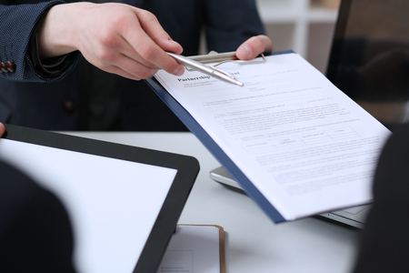 Male arm in suit offer contract form on clipboard pad and silver pen to sign closeup. Strike a bargain for profit, white collar motivation, union decision, corporate sale, insurance agent concept