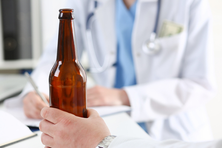 sobriety: Alcoholic hold in hand empty bottle at doctor reception office closeup. Grief and despair, intoxicated, change life, drunkenness lifestyle, sobriety and temperance, bad habit dependence concept Stock Photo