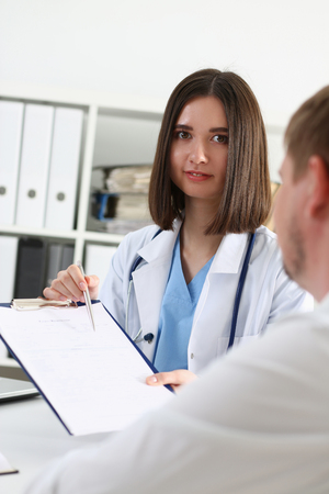 Female doctor hand hold silver pen and showing pad. Physical agreement form signature, disease prevention, ward round reception, consent contract sign, prescribe remedy, healthy lifestyle concept Stock Photo