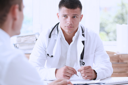 Handsome smiling male doctor hold silver pen fill patient history list at clipboard pad. Physical exam, 911, illness prevention, therapeutist ward round, prescribe remedy, healthy lifestyle concept