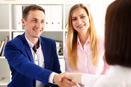 handclasp: Smiling man and woman shake hands as hello in office portrait. Friend welcome, mediation offer, positive introduction, greet or thanks gesture, summit participate approval, strike arm bargain concept Stock Photo