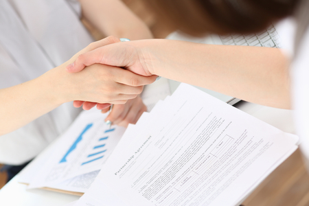 Businesswoman and woman shake hands as hello in office closeup. Friend welcome, introduction, greet or thanks gesture, product advertisement, partnership approval, arm, strike a bargain on deal concept