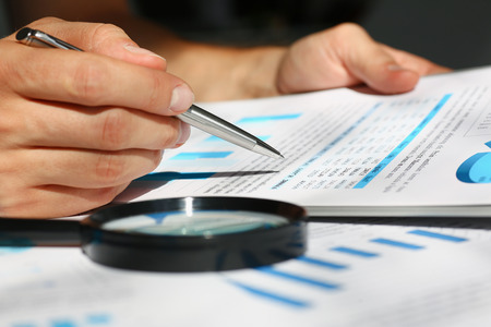 Financial statistics documents on clipboard pad at office table closeup. Internal Revenue Service inspector sum check, irs investigation, exchange market, earnings, savings, loan and credit concept Stock Photo