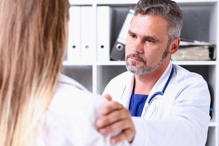 Friendly male doctor hold patient shoulder in office during reception. Examination result, positive test, calm down, promise and cheer up, grief and suffer, treatment, condolence, ethics concept