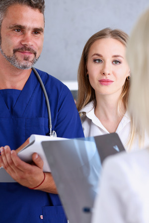 Smiling handsome doctor communicate with patient holding silver pen and showing pad. Physical agreement signature, disease prevention, interpreter, translator, prescribe remedy, healthy lifestyle Banque d'images