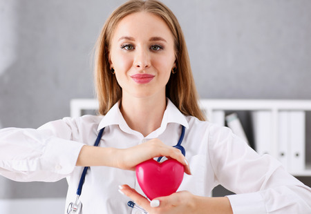 Beautiful smiling blond female doctor hold in arms red toy heart closeup. Cardio therapeutist, student education, CPR, 911 life save, physician make cardiac physical, pulse rate measure, arrhythmia