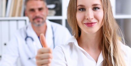 Woman show OK or confirm with thumb up at doctor office portrait. High level work, confident satisfied client do like, visit, best occupation, healthy life, emergency help, teamwork success concept