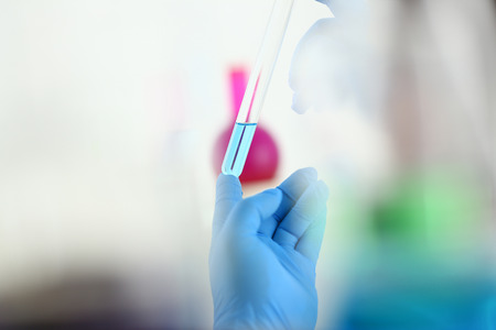 A male chemist holds test tube of glass in his hand overflows a liquid solution of potassium permanganate conducts an analysis reaction takes various versions of reagents using chemical manufacturing