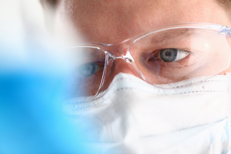 A portrait of a young surgeon chemists doctor looks at a container with a blue liquid and a mask is fought with viruses and a vaccine for vaccines against diseases