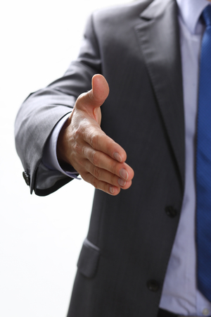 Man in suit and tie give hand as hello in office closeup. Friend welcome, mediation offer, positive introduction, thanks gesture, summit participate approval, motivation, male arm, strike bargain Stock Photo