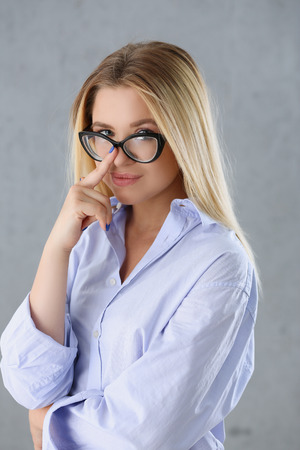 Portrait of a sexy woman in a mans shirt wearing glasses on a gray background looks at the camera and smiling look advice to give wants objections are not accepted